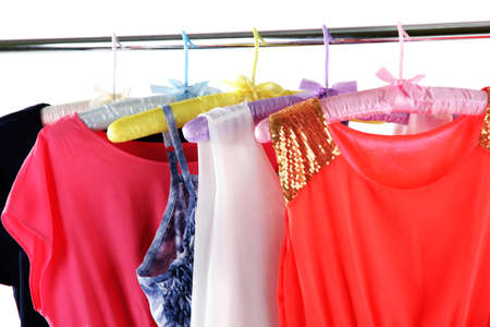 Beautiful dresses hanging on hangers isolated on white photo