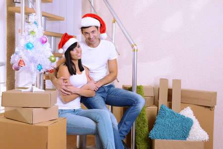 Young couple celebrating New Years in new home on stairs background photo