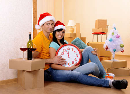 Young couple with boxes in new home celebrating New Years photo