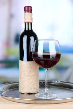 Wine glass and bottle on bright background photo
