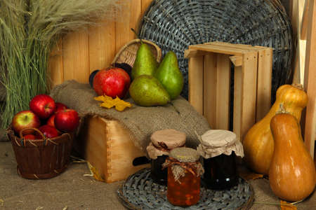 Fruits on crate with jar of jam and pumpkins on sackcloth on wooden background photo