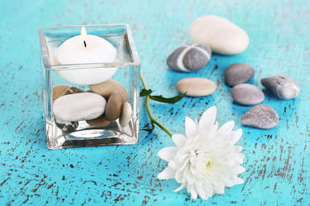 Decorative vase with candle, water and stones on wooden table close-up photo