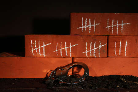 unfreedom: Counting days by drawing sticks on bricks on dark background Stock Photo