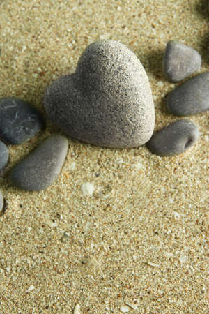 hardness: Grey stone in shape of heart, on sand background Stock Photo