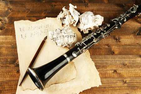 wastrel: Crumpled paper balls with music sheets and clarinet on wooden background Stock Photo