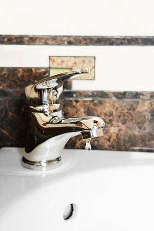 Ceramic sink with chrome fixture, close up photo