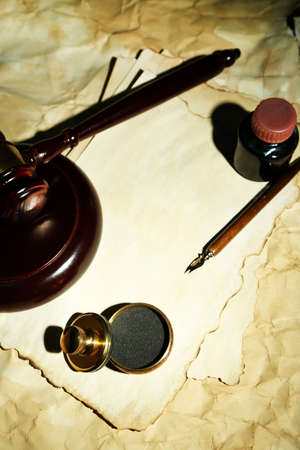 Wooden stamp, gavel and old papers, close up photo