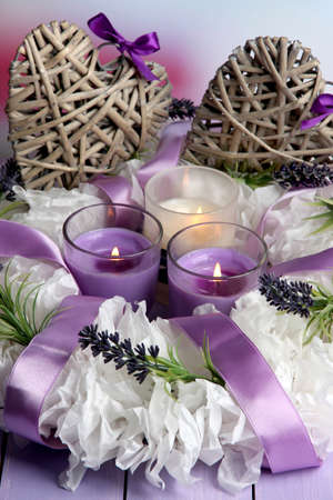 heats: Decorative wreath with candles and wicker heats on table on bright background