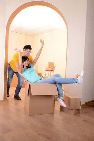 Young couple fooling around in new house on room background  photo