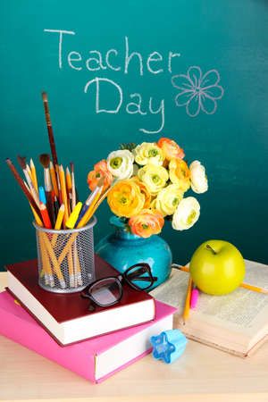 School supplies and flowers on blackboard background with inscription Teacher Day photo