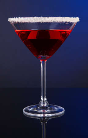 Red cocktail in martini glass on dark blue background photo
