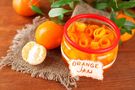 Orange jam with zest and tangerines, on brown wooden table photo