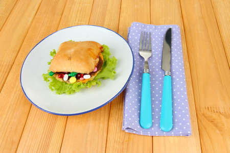 Conceptual image for nutritional care:assorted vitamins and nutritional supplements in bun. On wooden background photo