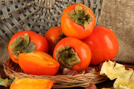 Ripe persimmons with nuts on table on wicker background Stock Photo