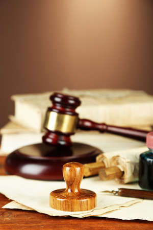 Wooden stamp, gavel and old papers on wooden table photo