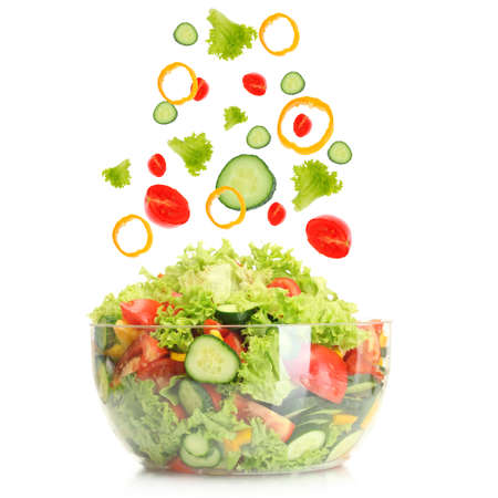 greek food: Fresh mixed vegetables falling into bowl of salad isolated on white Stock Photo
