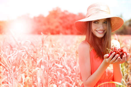 Portrait of beautiful young woman with berries in the field photo