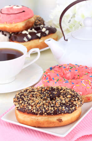 Sweet donuts with cup of tea on table close-up photo