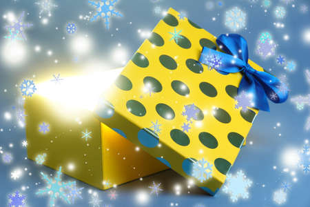 Gift box with bright light on it on blue background photo