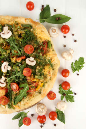 Tasty vegetarian pizza and vegetables on wooden table photo