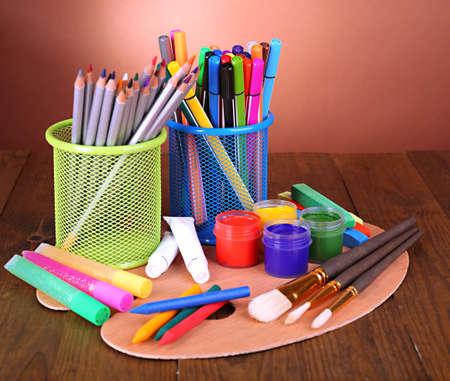 creative tools: Composizione di diversi strumenti creativi sul tavolo su sfondo marrone