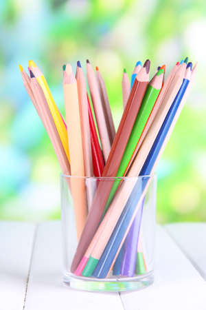 metall and glass: Colorful pencils in glass on wooden table on natural background Stock Photo