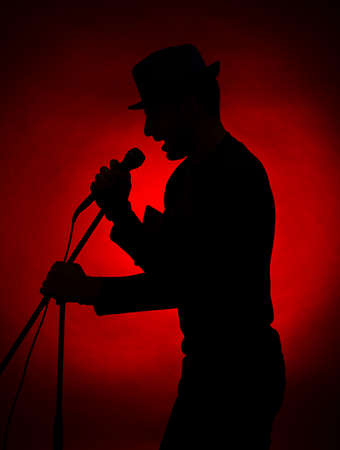 Musician silhouette on dark color background photo