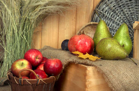 Apples in basket and fruits on crate on sackcloth on wooden background photo