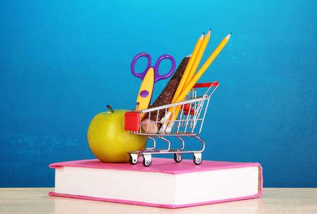 School supplies in supermarket cart on blackboard background photo