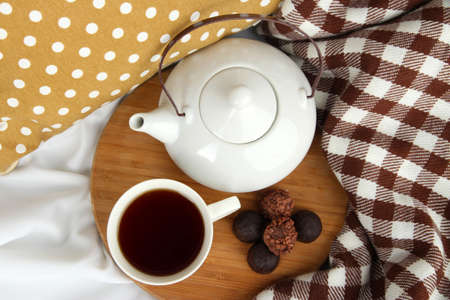 stand teapot: Cup and teapot with candies on wooden stand on bed close up Stock Photo