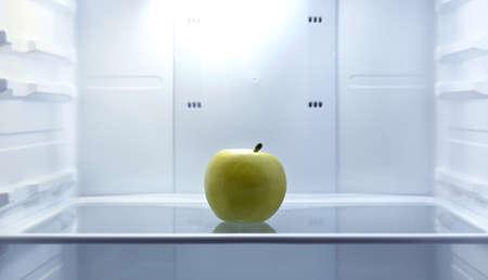 開いている空の冷蔵庫に 1 つのリンゴ。重量損失の食事療法のコンセプトです。