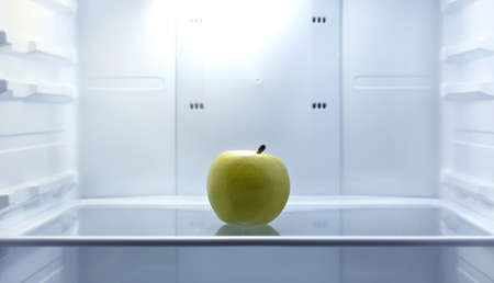 refrigerator: One apple in open empty refrigerator. Weight loss diet concept.