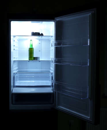 One  beer bottle and canned tune in open empty refrigerator: bachelor fridge concept. photo