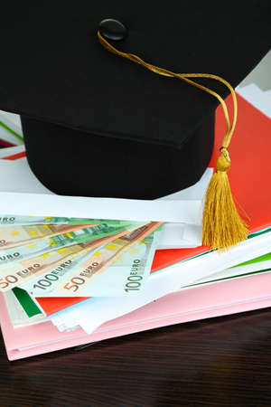 the alumnus: Money for graduation or training on wooden table close-up Stock Photo