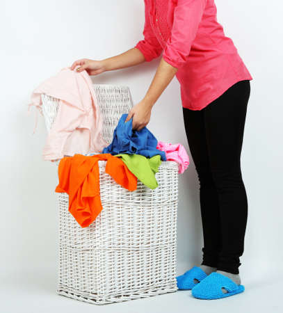 Woman with full laundry basket on gray background photo