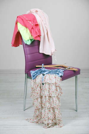 slut: Heap of  clothes on color chair,  on gray
