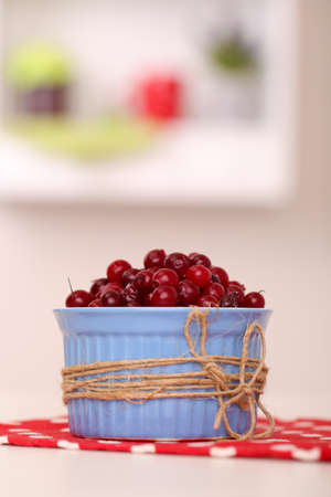 Ripe red cranberries in bowl on table  photo