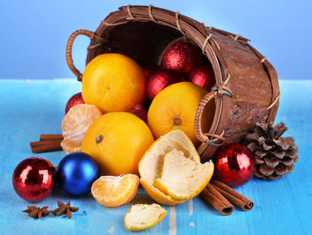 Christmas tangerines and Christmas toys in basket on blue  photo