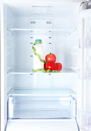 Conceptual photo of diet: apple and milk bottle with measuring type on shelf of refrigerator Stock Photo - 24341103