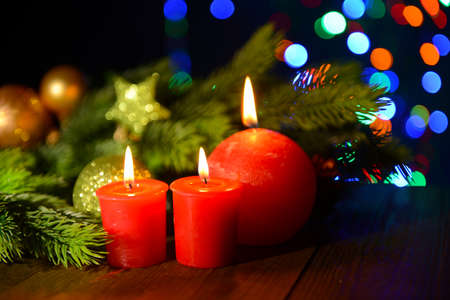 Composition with burning candles, fir tree and Christmas decorations on multicolor lights  photo
