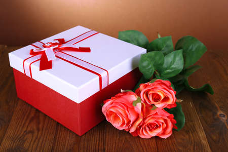 Beautiful gift box with flowers on table on brown  photo