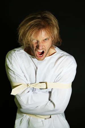 psychopathe: Malades mentaux homme en camisole de force sur fond noir