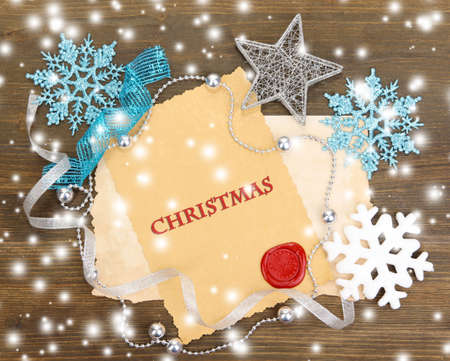 Frame with vintage paper and Christmas decorations on wooden background photo