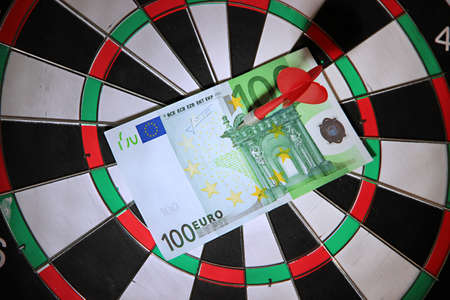 Money pierced by arrow on dartboard close up photo