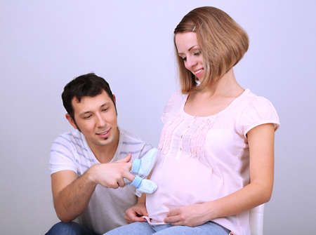 Young pregnant woman with her husband holding baby shoes on gray background photo
