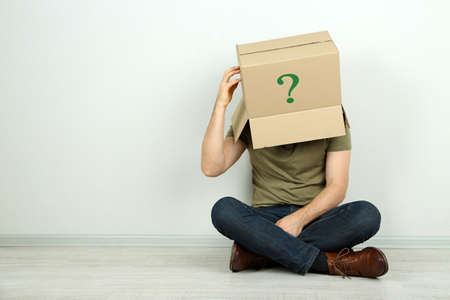 recognize: Man with cardboard box on his head sitting on floor near wall