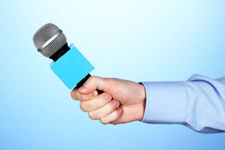 Male hand with microphone on blue background photo
