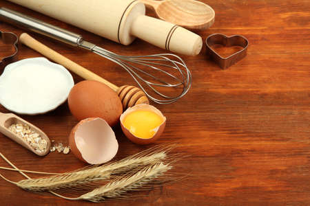 Cooking concept. Basic baking ingredients and kitchen tools on wooden table photo