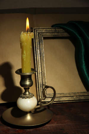 Old candle on table in room photo