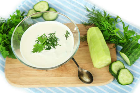 Cucumber yogurt in glass bowl, on color napkin, isolated on white photo